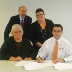 Judith Kiejda and Brett Holmes (back right and front right) signing the agreement with NSW Health