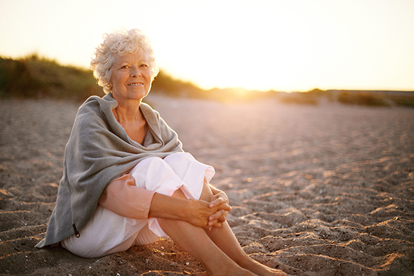 Relaxed retired woman wearing shawl sitting on sandy beach. Old caucasian woman sitting on the beach looking at camera outdoors